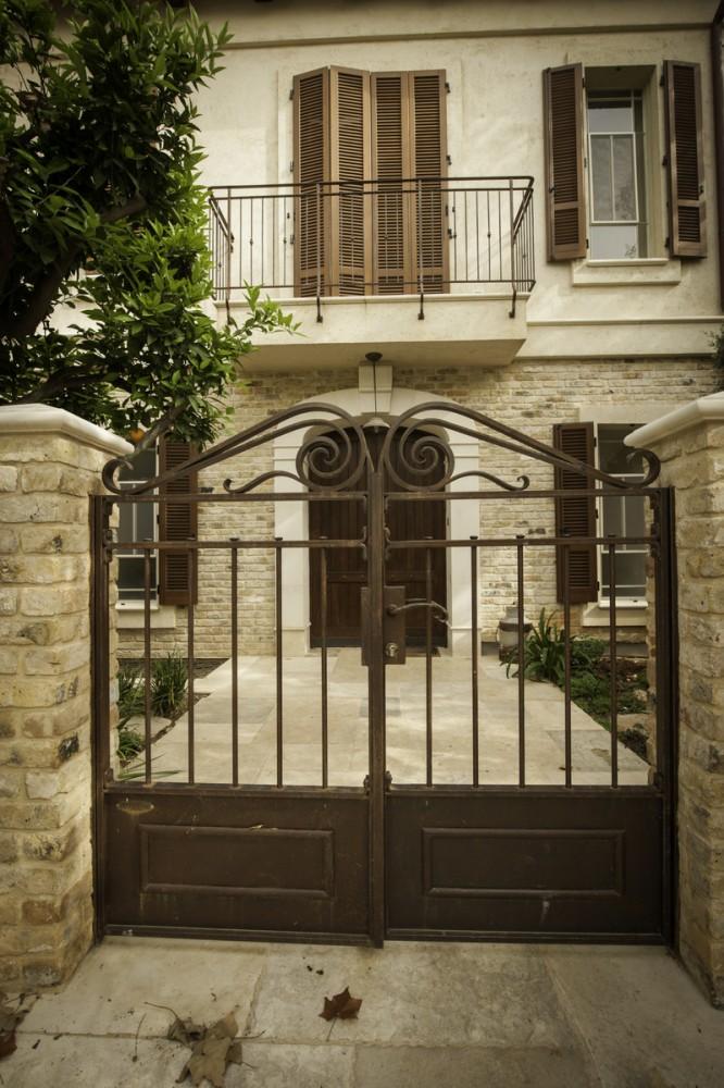 שער כניסה בעיבוד חלודה טבעית עם עיטורי נפחות ומעליו מעקה המרפסת - בית אור