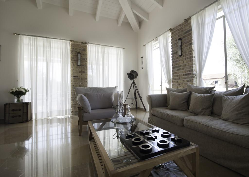 פינת הישיבה בסלון מוקפת בויטרינות פרופיל בלגי ברזל עם וילונות קלילים לבנים – הבית הלבן ארטפרו