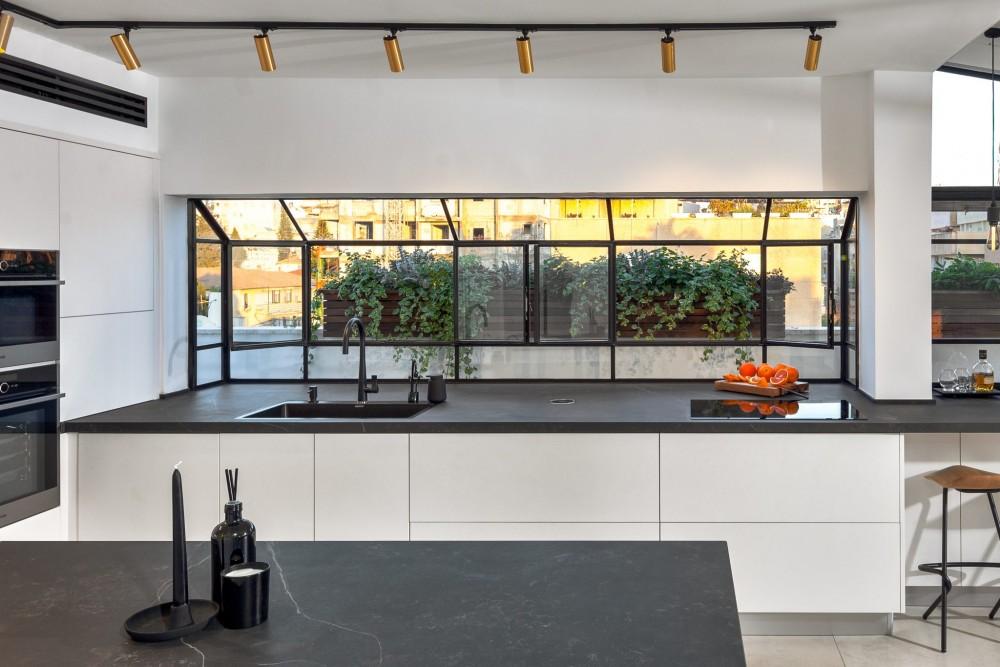 חלון bay גדול לכל אורך המטבח מכפיל את משטח השיש.