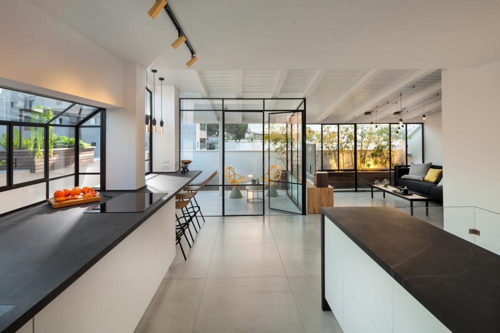 הסלון נפתח אל המרפסת על ידי ויטרינות פרופיל בלגי בעיצוב מינימליסטי