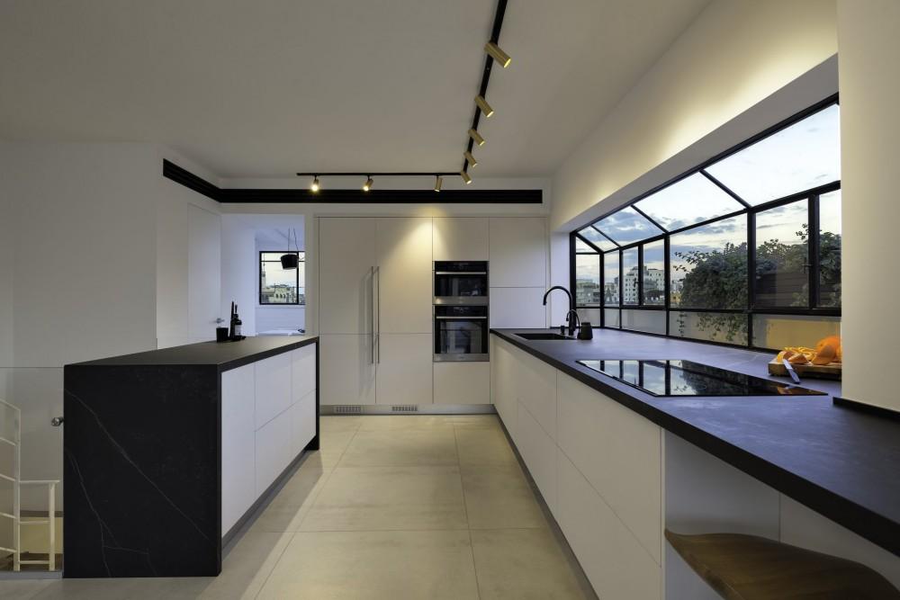חלון bay גדול לכל אורך המטבח מכפיל את משטח השיש. מזוית נוספת