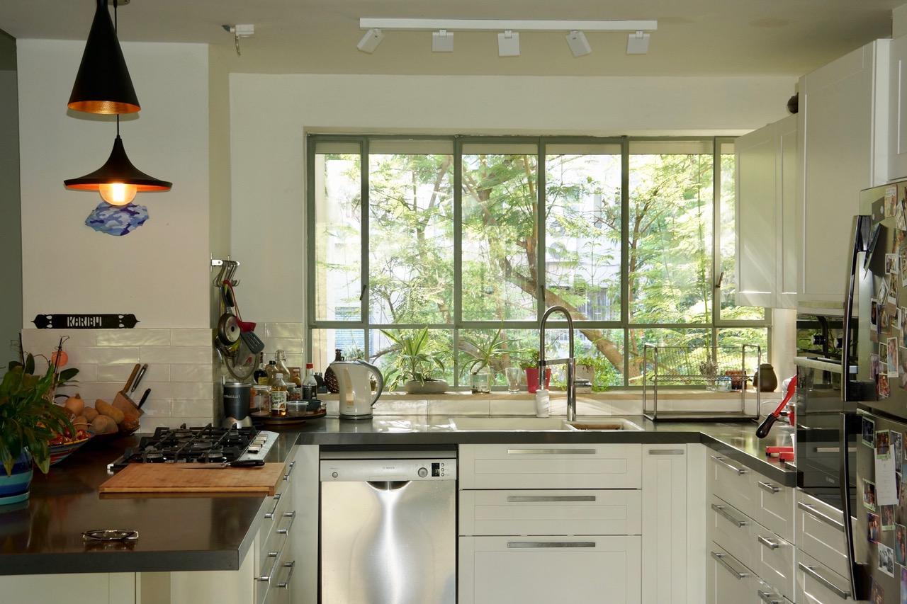 חלון המטבח שמכניס הביתה אור רב וכן את צמרות העצים