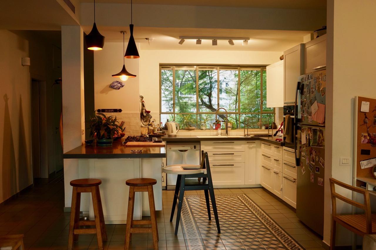 מבט אל חלון המטבח שמכניס הביתה את צמרות העצים