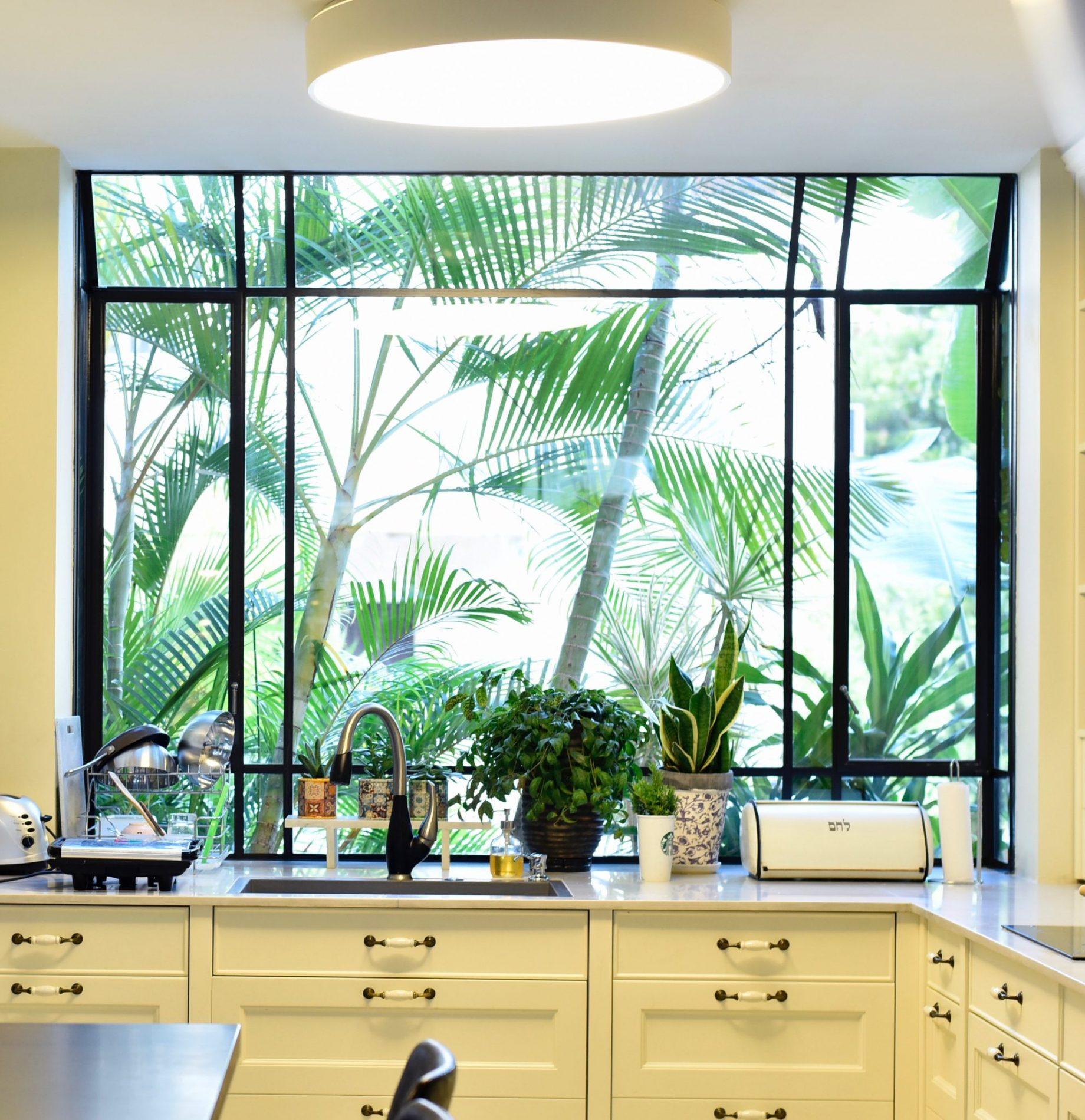 חלון bay מפרופיל בלגי שחור במטבח, מכניס את הגינה אל תוך הבית. – פרוייקט ארטפרו באור יהודה
