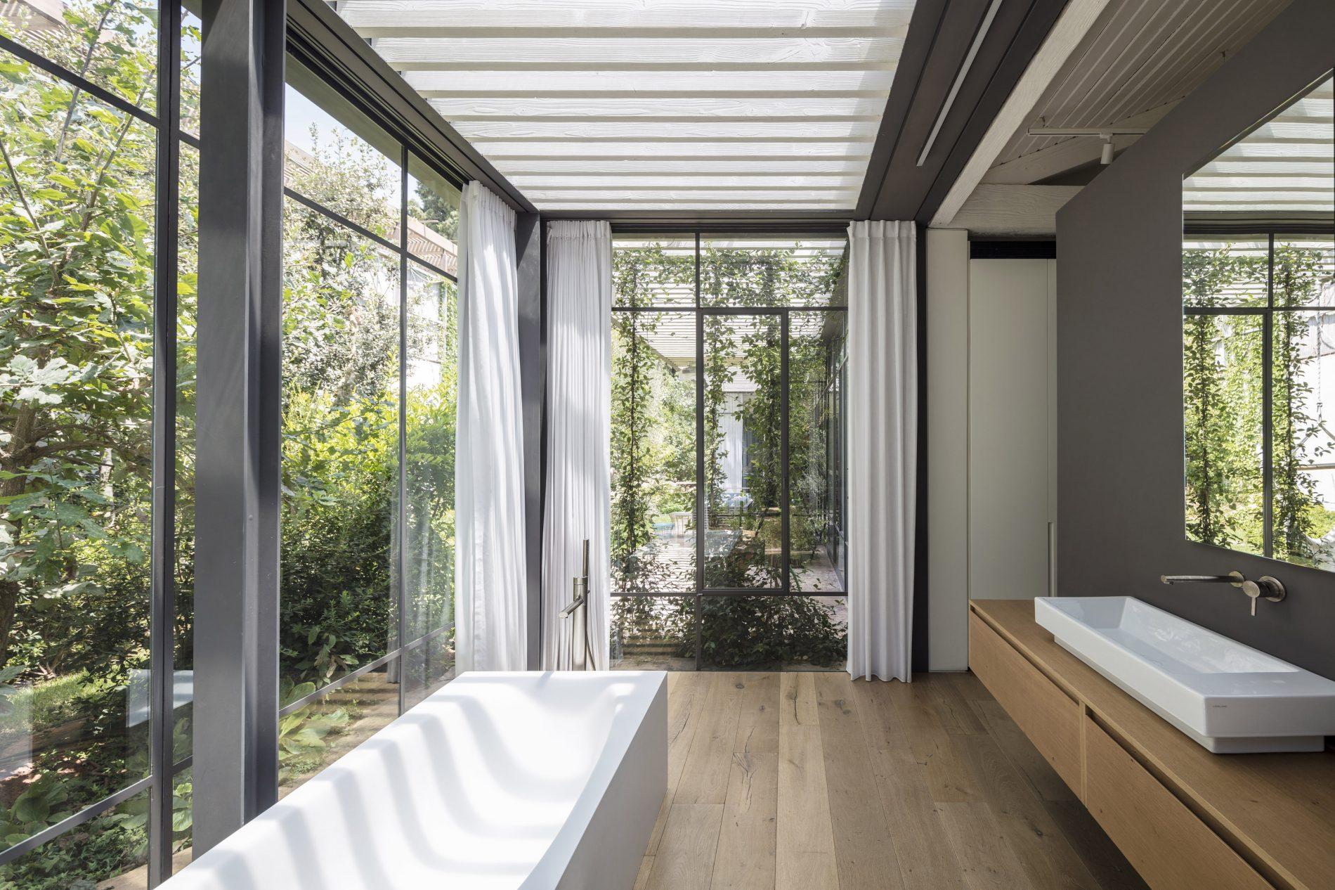 אמבט הורים עטוף בפרופיל בלגי שקוף, נותן הרגשה מרגשת של רחצה בטבע - בית הזכוכית