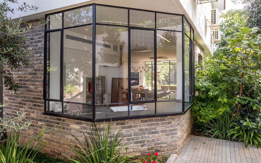 חלון צורני גדול במטבח פותח את הבית לגינה – בית האדריכל מיקי אורן